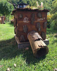 Une maison en bois avec un tronc pour hérisson